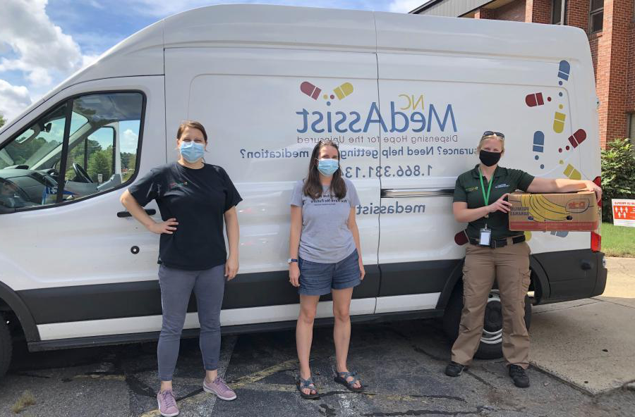 three people st和ing in front of a MedAssist van with masks
