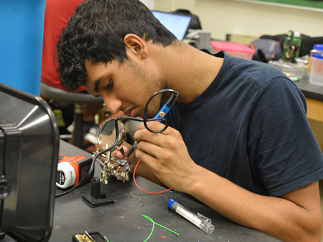 A student in the associate in engineering program at Durham Tech uses a tool to work on a metal trinket in class.