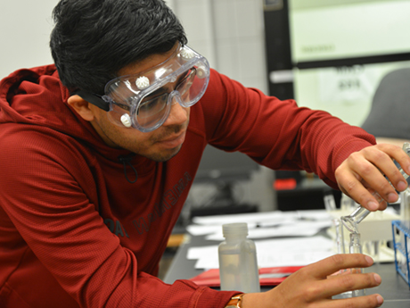 A male student in the Associate in Science program pours liquid into a beaker in a chemistry classroom.