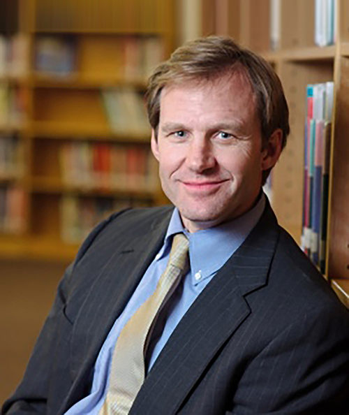portrait of JB Buxton wearing a suit and tie sitting in a library