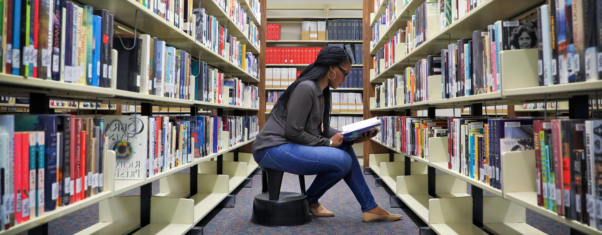 female student sitting on a step stool reading a book she just pulled from the library shelf
