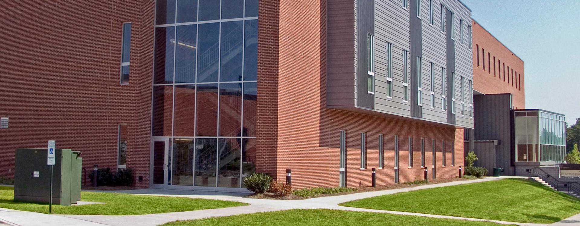 brick, gray panel, and glass campus building