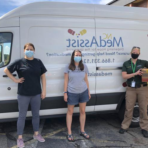 three people standing in front of medassist truck smiling and wearing masks