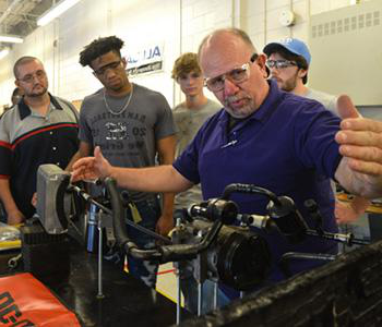 an instructor demonstrating to a small group of students how to use automotive machinery