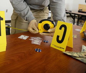 criminal justice student practicing crime scene analysis with signs and measuring tape