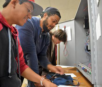 students standing in front of electronic equipment