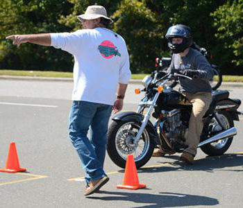 person on motorcycle is directed by instructor to ride between cones