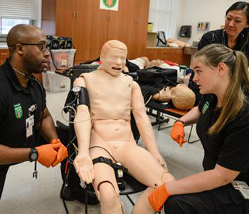 EMS students performing advanced training with a dummy
