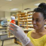 student with gloves holding bottle with medicine