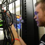 An information technology program student looks at a multi-colored server with LED lights as the student uses his hands to work on the server.