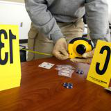 Evidence markers sit on a desk as a 刑事司法技术 student measures the distance between areas of a training crime scene.