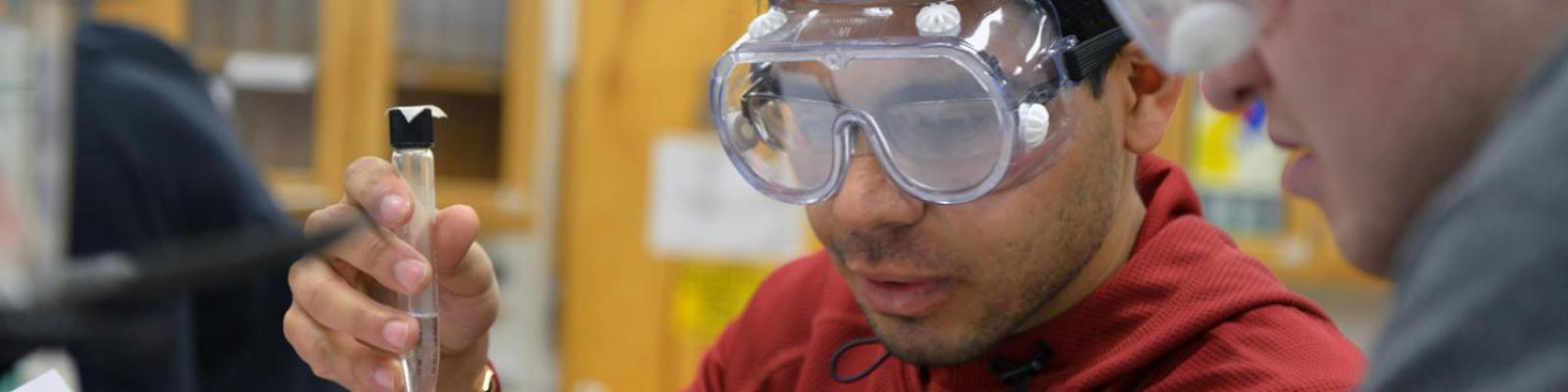student wearing goggles performing chemistry experiment